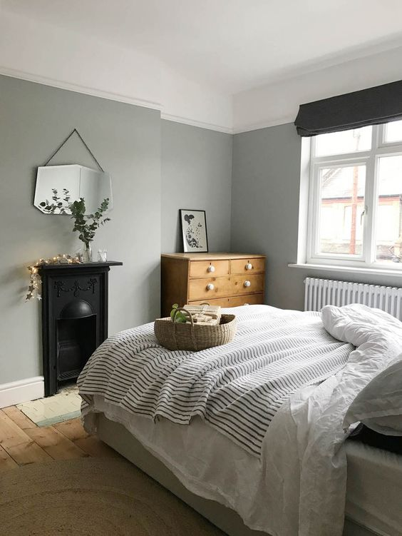 a Nordic bedroom with grey walls, a vintage built in hearth, a bed with neutral and printed bedding, a stained dresser and a mirror