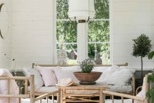 a Nordic veranda with bamboo furniture and neutral and printed textiles, potted greenery and a tree plus a pendant lamp
