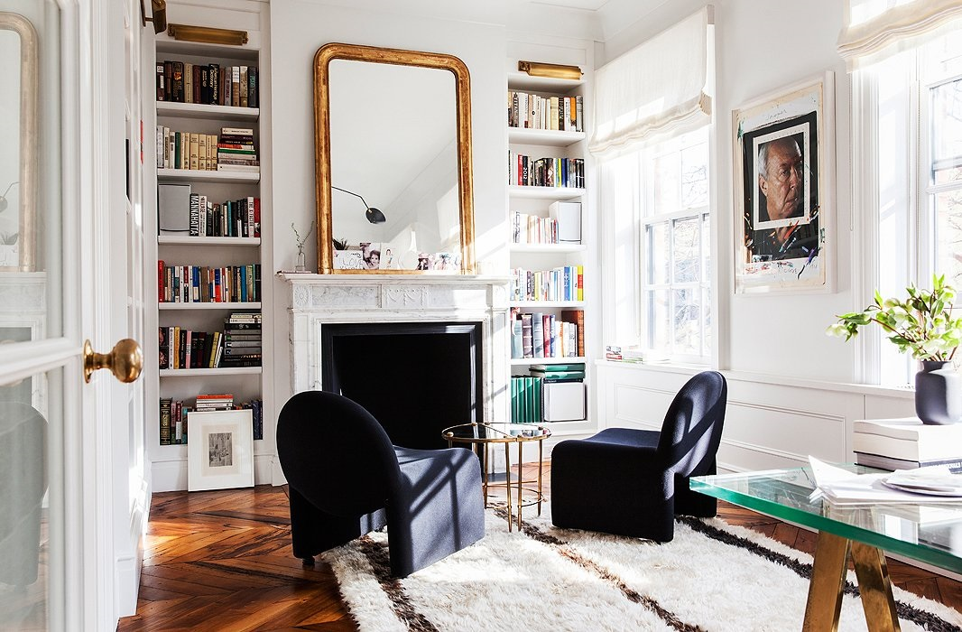 a Parisian chic home office with built in shelves, a fireplace, navy chairs and a glass table, a glass desk and some art