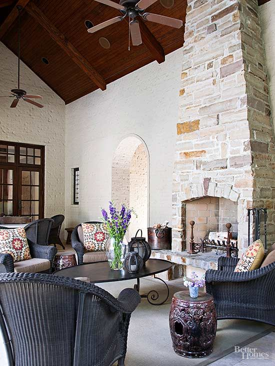 a Provence-inspired outdoor space under a roof with a stone fireplace, black wicker furniture and a black low table, printed textiles