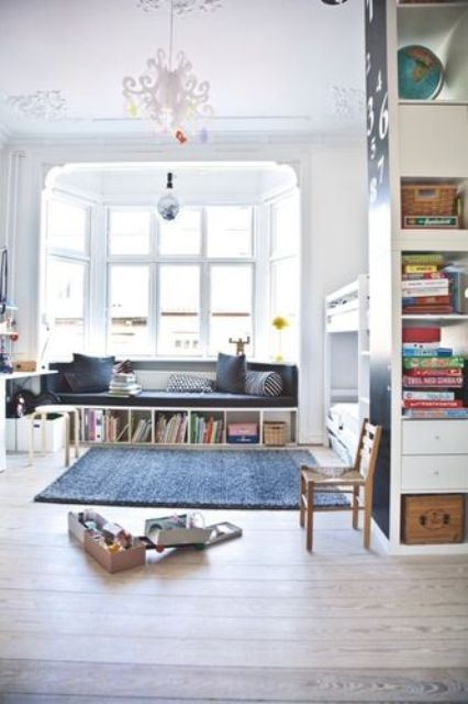 a Scandinavian kid's room with a bunk bed, a bow window with a windowsukk daybed and some storage compartments