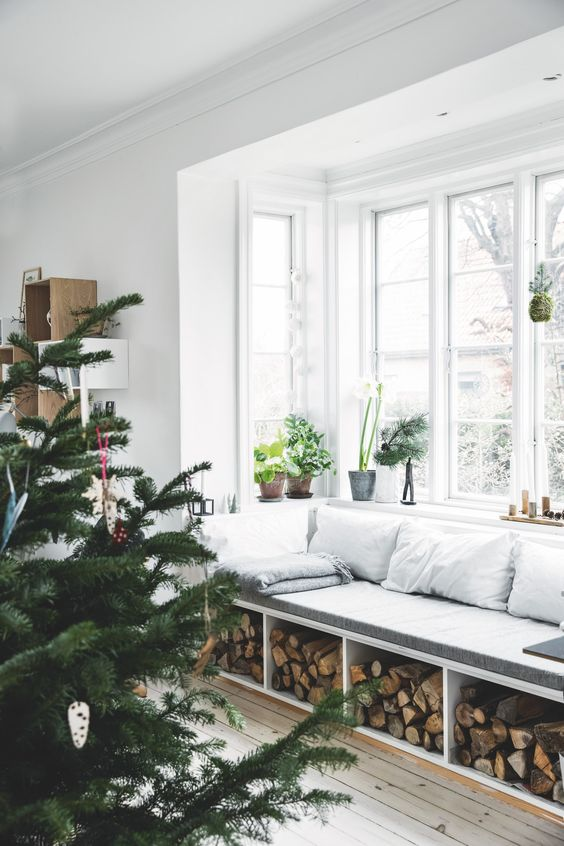 a Scandinavian space with a bow window, a windowsill daybed with firewood storage and lots of potted greenery is very cozy