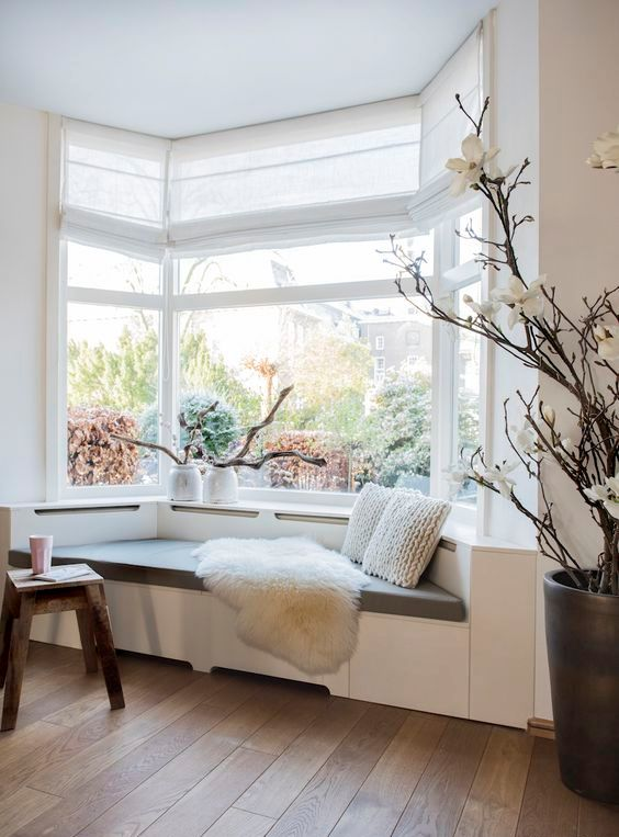 a Scandinavian space with a large bow window and an upholstered daybed by its side plus driftwood arrangements on the windowsill