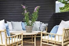 a Scandinavian terrace with a wooden deck, bamboo furniture, muted and neutral textiles and string lights
