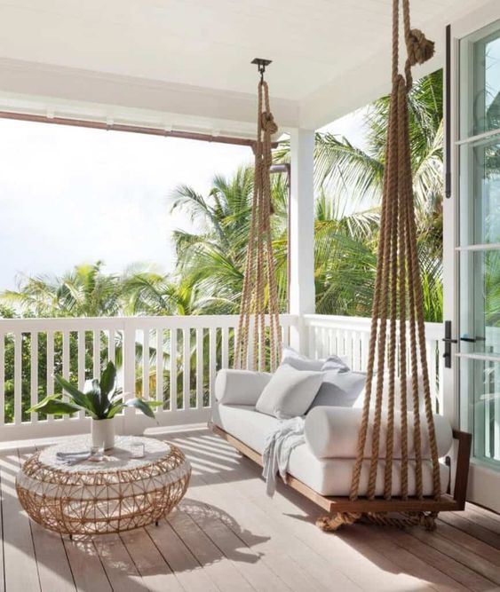a back porch with a hanging daybed with pillows on multiple ropes, with a chic and delicate coffee table plus potted greenery