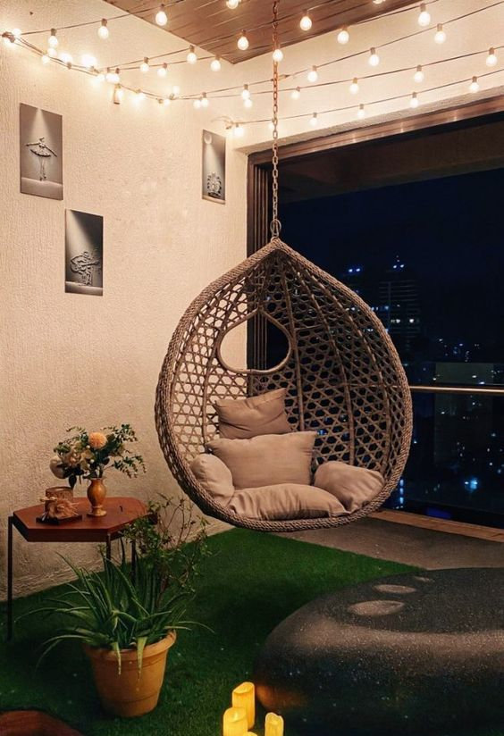 a balcony styled as an outdoor space, with artificial grass, potted plants and blooms, a pendant rattan chair, a large rock and some artworks
