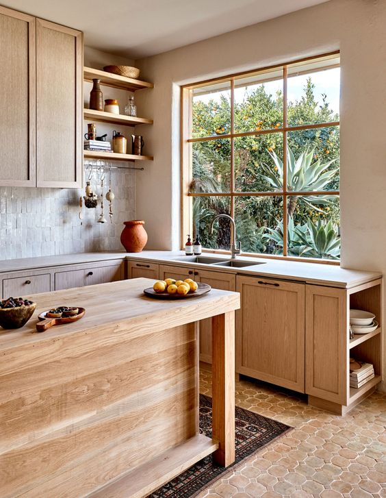 a beautiful Mediterranean kitchen with light stained cabinets, stone countertops, a kitchen island and open shelves