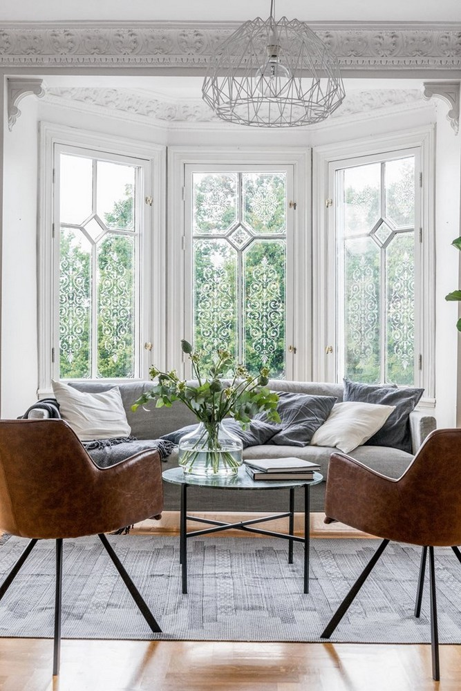 a beautiful Parisian chic living room with a bow window with refined frames, a grye sofa that is placed in the niche, chic furniture and molding on the ceiling