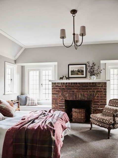 a beautiful bedroom with grey walls, a bed with printed bedding, a red brick fireplace and a windowsill daybed and a printed chair