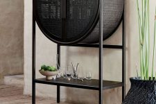 a beautiful black cane home bar of a round shape and with an open shelf is a lovely idea for a modern and refined space
