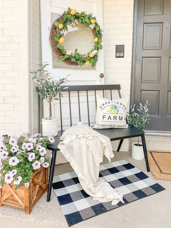 a beautiful farmhouse porch with a black bench, a printed  rug, a lemon wreath and potted plants and blooms is a lovely space to spend some time