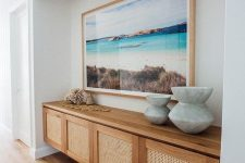 a beautiful floating credenza with cane doors is a stylish idea that matches a coastal space perfectly and looks amazing
