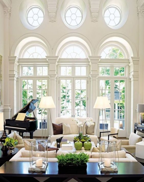 a beautiful living room with neutrals and dark touches, with double height French windows and round ones, with lots of greenery