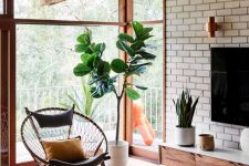 a beautiful modern living room with a brick accent wall, a corner daybed, chic furniture and potted plants and a lovely view of the garden