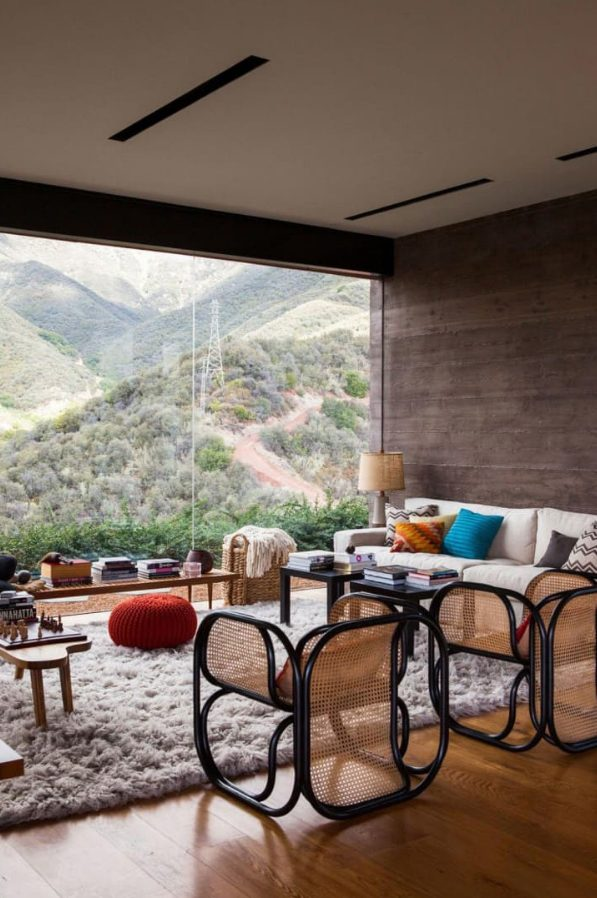 a beautiful modern living room with a panoramic view, with chic furniture and lovely black cane chairs, lots of books and colorful pillows