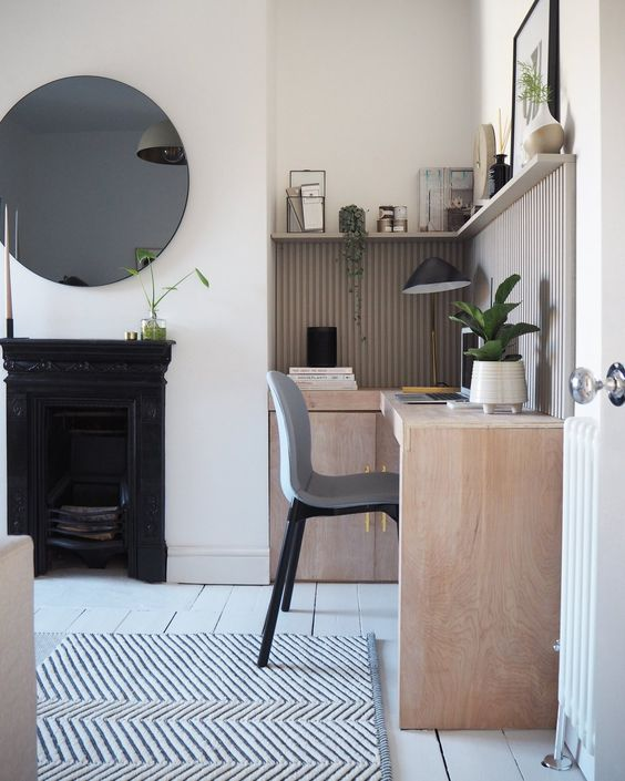 a beautiful neutral home office with a metal fireplace, a neutral corner desk, a grey chair, a long shelf, a round mirror and a printed rug