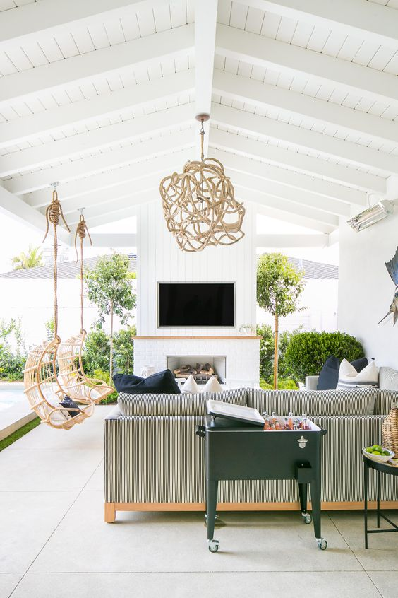 a beautiful outdoor living room with a white fireplace, a striped corner sofa, printed pillows, hanging rattan chairs and an antler chandelier