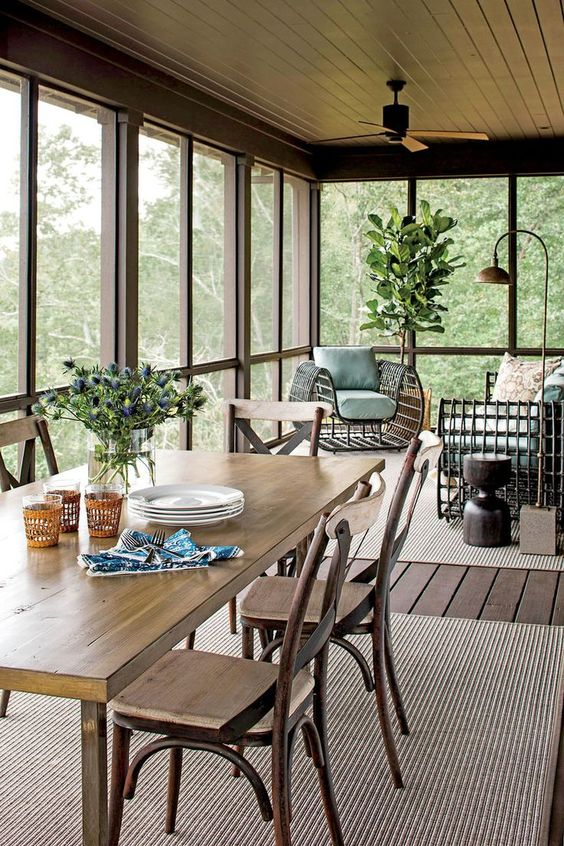 a beautiful screened porch with a simple wooden dining set, bold rattan seating furniture, some greenery and lamps is cool