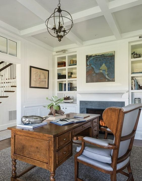 a beautiful vintage home office with a built-in fireplace, built-in shelves, artworks, a vintage heavy desk and a wingback chair is chic