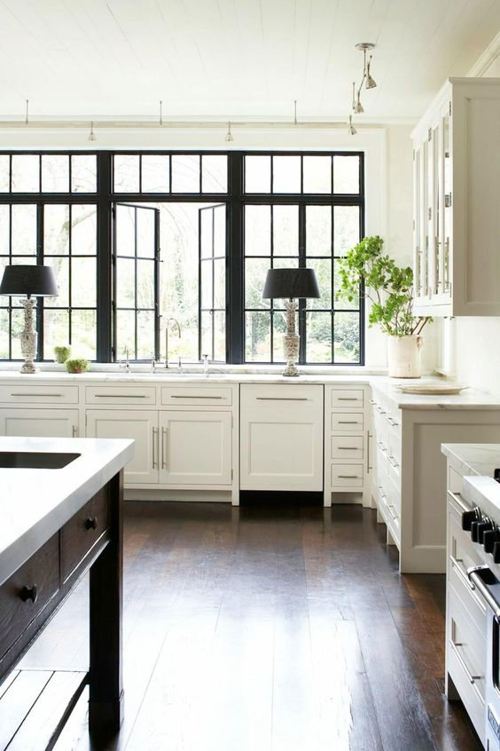 a beautiful vintage kitchen done in black and white, with black French windows and some other touches that create a drama