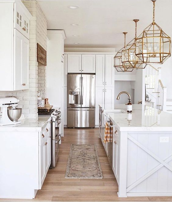 a beautiful white farmhouse kitchen with exposed brick walls, brass pendant lamps, chrome appliances and fixtures is cool