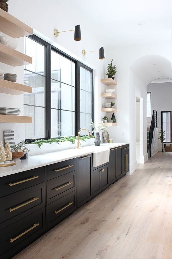 a black farmhouse kitchen with shaker style cabinets and black French windows, open shelves, black and gold sconces and greenery