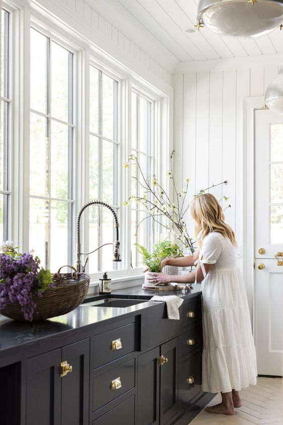 a black kitchen with gold knobs and a chromatic faucet, gold knobs on the door make the space look very stylish and very chic