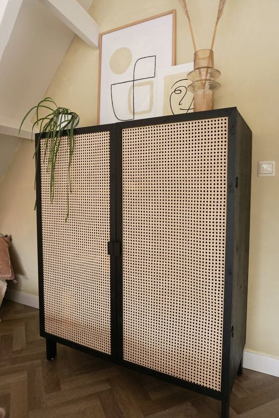 a black storage unit with cane doors is a bold and cool storage unit that looks lightweight at the same time