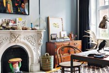 a boho eclectic home office with blue walls, an ornated fireplace, printed layered rugs, a dark desk and a rattan chair, a stained sideboard