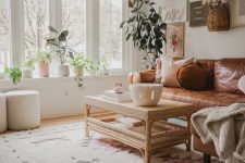 a boho living room with a leather sofa, a rattan table, a gallery wall and potted plants filled with light through a bow window
