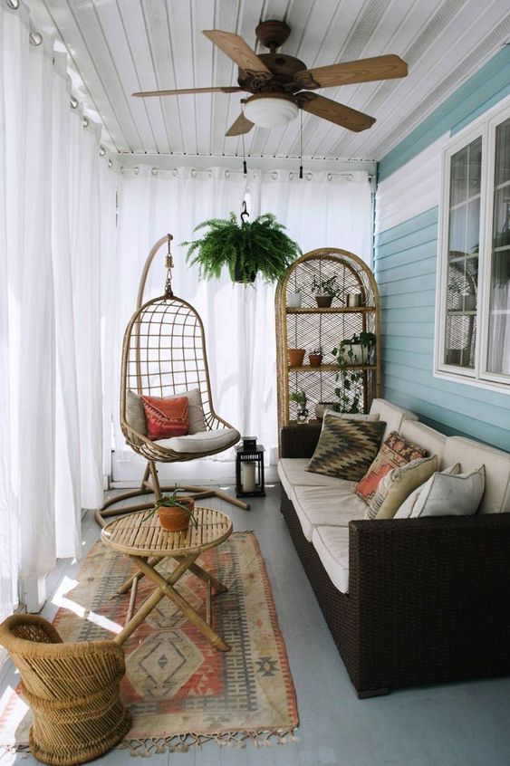 a boho porch with a printed boho rug, a small rattan chair and a big hanging one, a folding table, a wicker sofa and a storage unit
