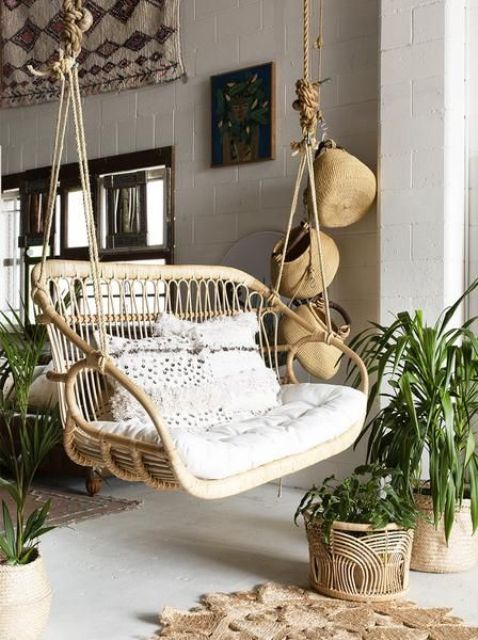 a boho porch with jute rugs, potted greenery, a rattan hanging double chair and some baskets hanging for decor