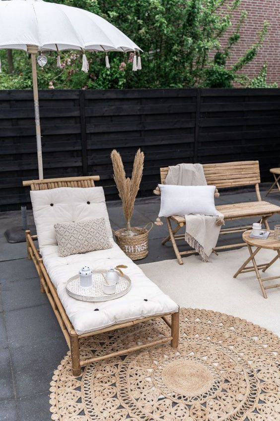 a boho terrace with a tiled floor, bamboo furniture, pampas grass in baskets, an umbrella with neutral bedding