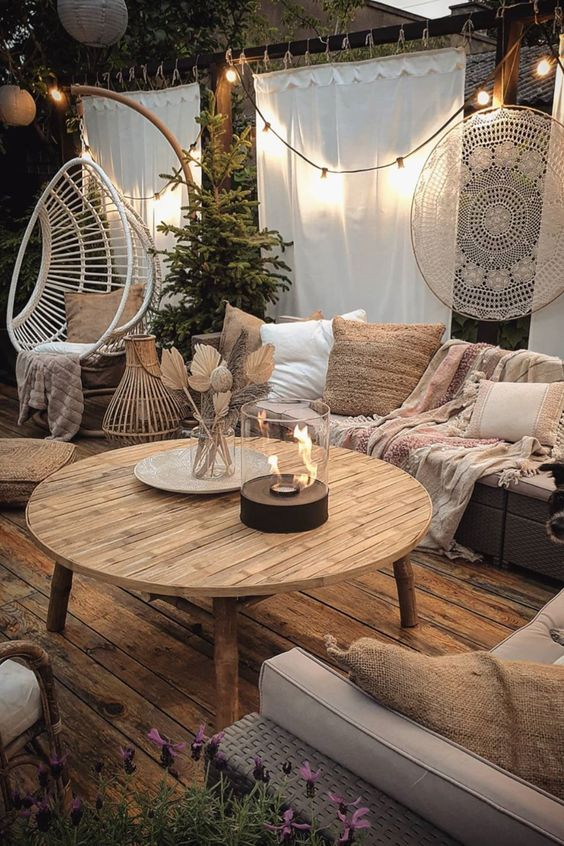 a boho terrace with cool wicker furniture and printed cushions and pillows, a white suspended chair on a stand, some string lights and a table fire pit