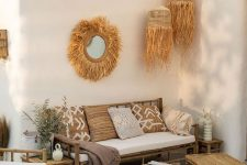 a boho tropical patio with bamboo furniture, neutral and printed textiles, pendant woven lamps, potted greenery is chic