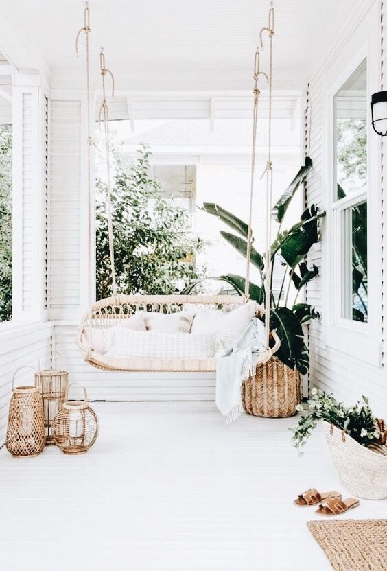 a boho tropical porch with a hanging rattan daybed, potted plants, a jute rug and some woven candle lanterns is a chic space to be