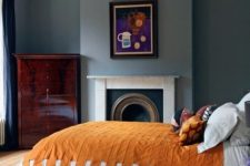 a bold and chic bedroom with grey walls, a fireplace, a dark stained dresser, a bed with bright bedding and a cool and bold artwork