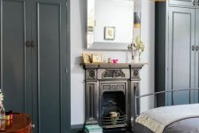 a bold and dark bedroom with graphite grey wardrobes, a metal bed with grey bedding, a built-in fireplace, a fringe pendant lamp and a dark stained vanity