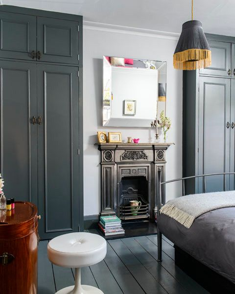 a bold and dark bedroom with graphite grey wardrobes, a metal bed with grey bedding, a built in fireplace, a fringe pendant lamp and a dark stained vanity