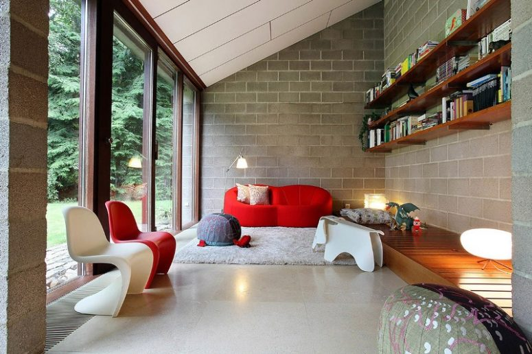 a bold and lovely mid-century modern living room with concrete walls, a hot red sofa and a chair, a white chair, open shelves and a platform