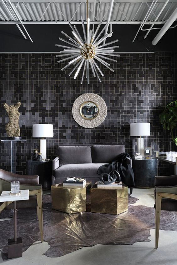 a bold and very statement space with printed wallpaper, a graphite grey sofa, black side tables, faceted gold coffee tables, chairs with gold legs and brass touches