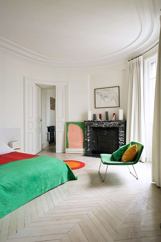 a bold bedroom with a fireplace clad with black marble, a bed with colorful bedding, a bold green chair and an artwork, a ceiling with molding
