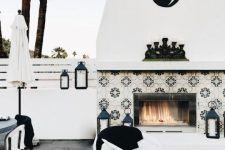 a bold black and white terrace with a lovely fireplace clad with tiles, candle lanterns, printed textiles and rattan chairs is amazing