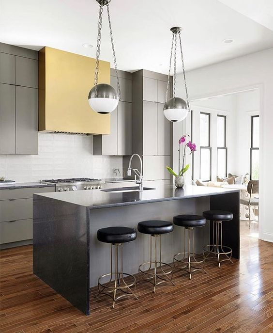 a bold contemporary kitchen with grey cabinets, a yellow hood, a grey ktichen island, chromatic fixtures, black stools with brass legs and pendant lamps with a silver finish