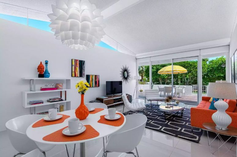 a bold living room with an orange sofa and a graphic rug, an oval table, white leather chairs, a TV unit and colorful artworks