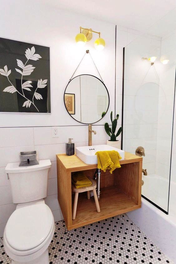 a bold mid-century modern bathroom with black and white penny tiles on the floor, a floating vanity, a round mirror and yellow touches