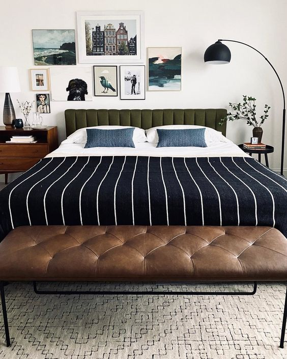 a bold mid-century modern bedroom with a green upholstered bed, navy printed bedding, a brown leather bench, stained nightstands and a pretty gallery wall