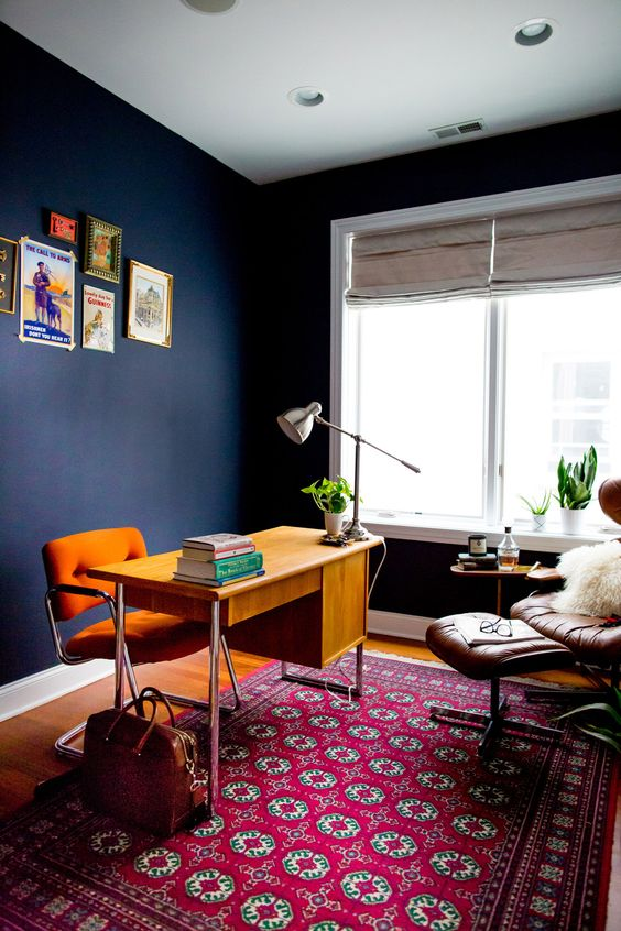 a bold mid-century modern home office with navy walls, a bright stained desk, an orange chair, a leather lounger, a bright printed rug, a colorful gallery wall and potted plants