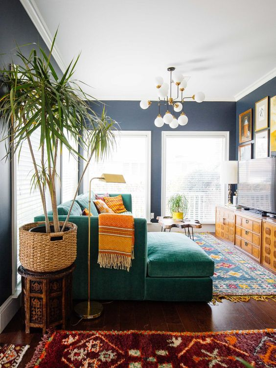 a bold mid-century modern living room with colorful printed rugs, an emerald sectional, printed pillows, stained storage unit and a colorful gallery wlal