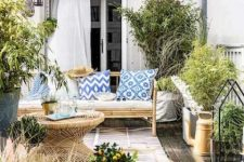 a bright Mediterranean deck with bamboo furniture, blue printed pillows, potted greenery and blooms and lovely terracotta vases